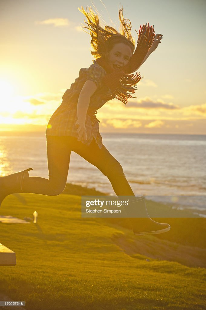 girl leaping in the air near the ocean : Stock Photo
