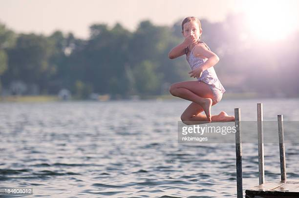 Girl leaping into lake