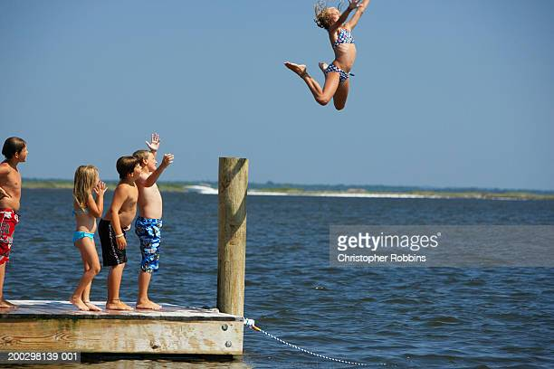 Girl (10-12) leaping off jetty, friends watching