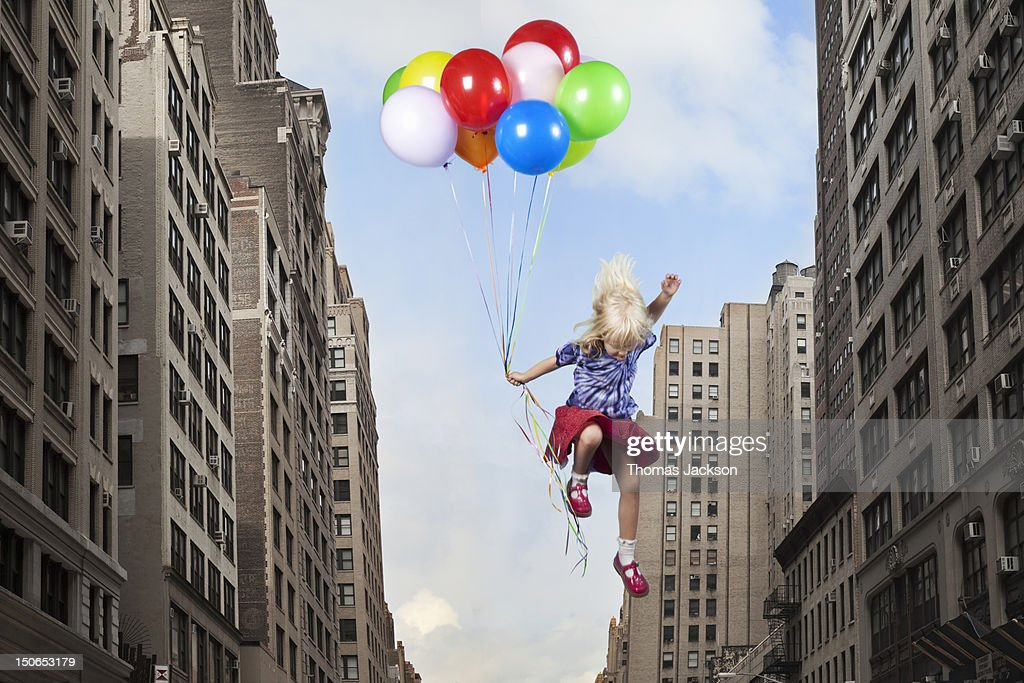 Girl leaping with balloons : Stock Photo