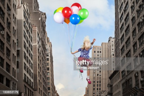 Girl leaping with balloons : Stock-Foto