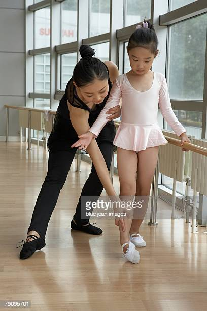 A girl learning ballet with her teacher.