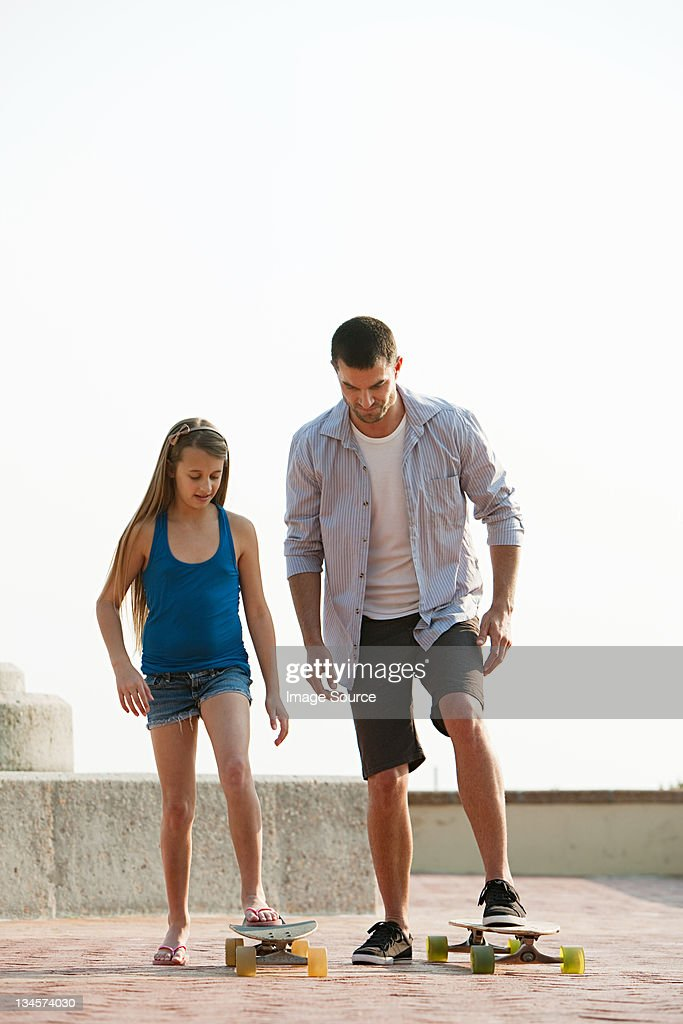 Girl learning how to use a skateboard : Stock Photo