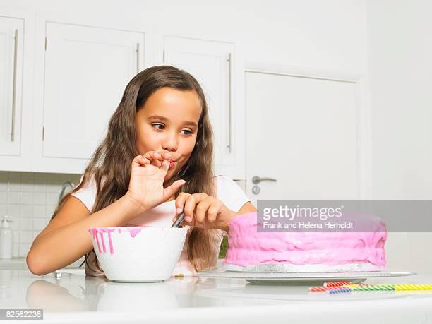 Girl licking finger by iced cake