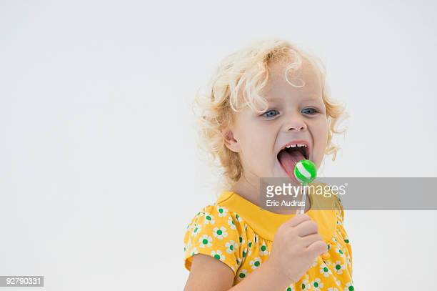Girl licking green lollipop