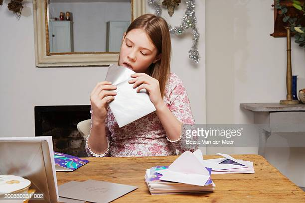 Girl (10-12) licking seal on envelope at table by christmas cards