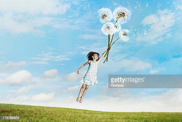 Girl lifted into the air clutching dandelions