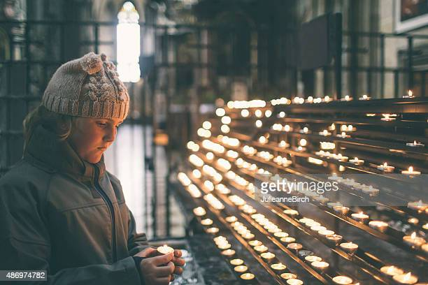 Girl lighting a candle in remembrance