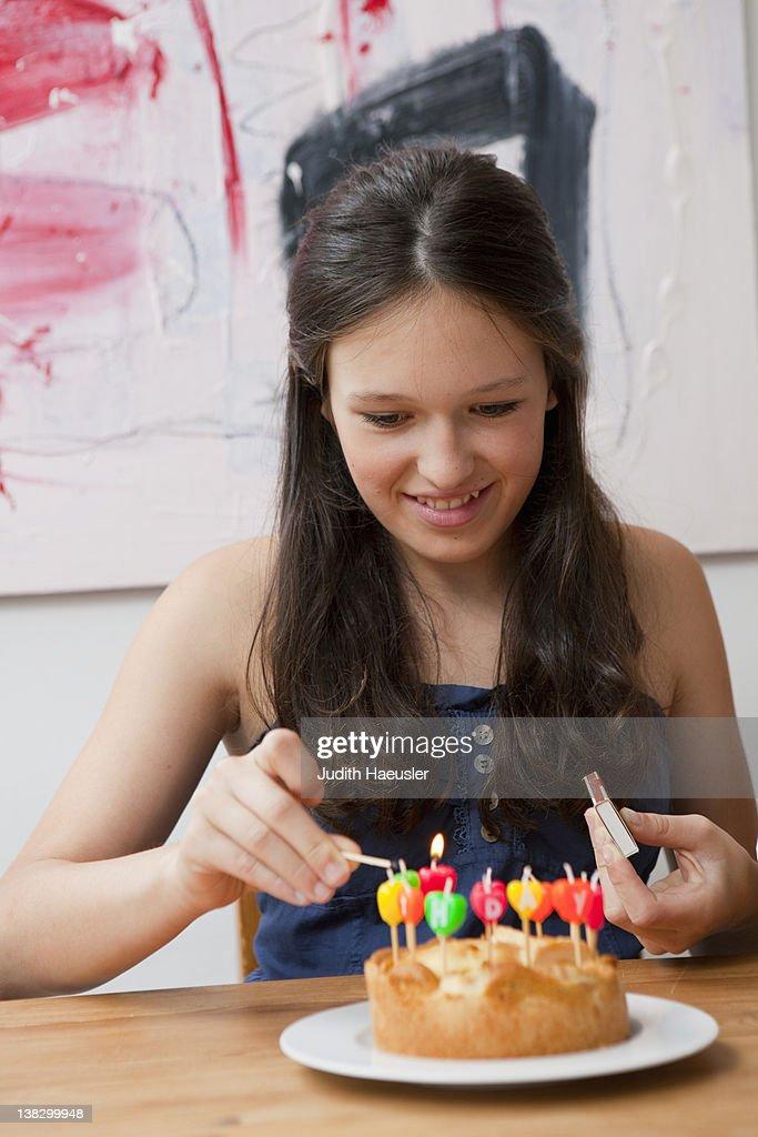 Girl lighting candles in birthday cake : Stock Photo