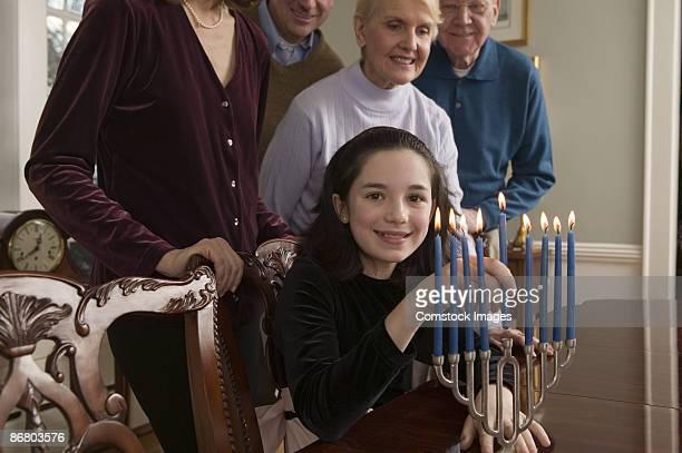 Girl lighting menorah