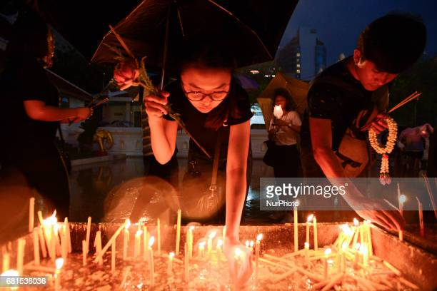 A girl lights a candle to celebrate during a ceremony marking Visakha Bucha Day in Bangkok Thailand on 10 May 2017 Visakha Bucha Day on the fullmoon...