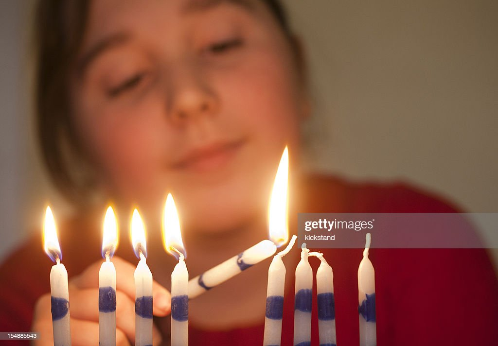 Girl lights menorah