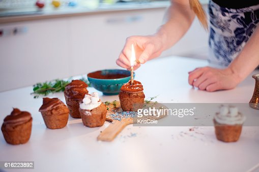 Girl lights the candle, decorates New Year celebration cupcakes, chocolate : Stock-Foto
