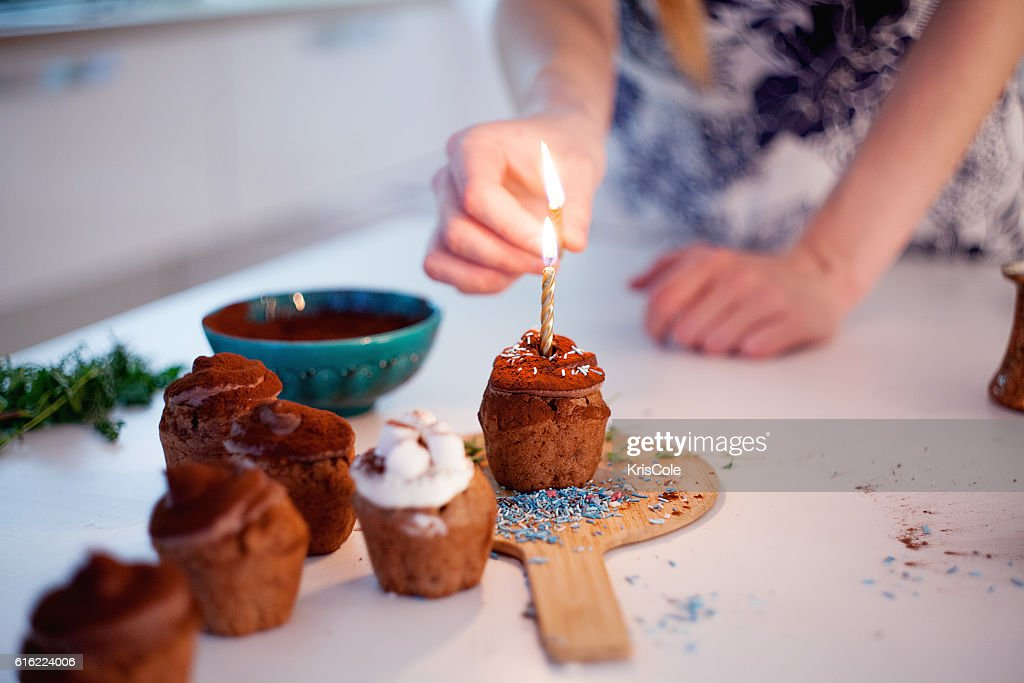Girl lights the candle, decorates New Year celebration cupcakes, chocolate : Stock Photo