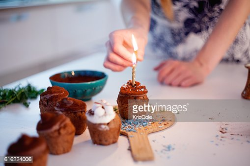 Girl lights the candle, decorates New Year celebration cupcakes, chocolate : Stockfoto