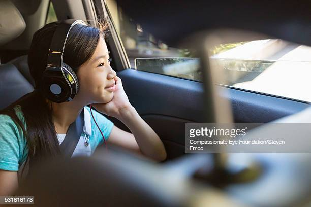 Girl listening to headphones in back seat of car