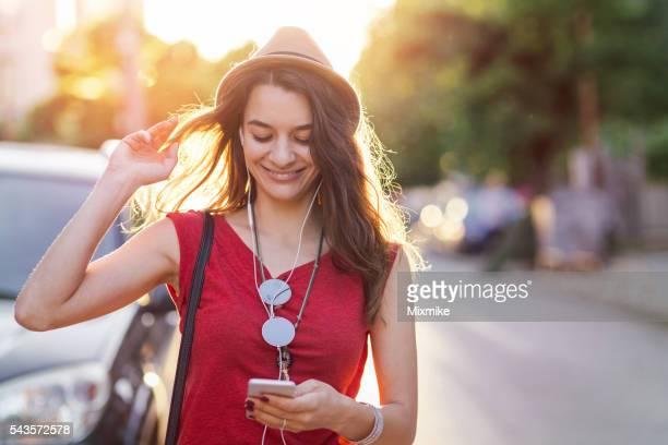 Ragazza ascolta la musica e ricevere tweet e messaggi di testo sul telefono cellulare