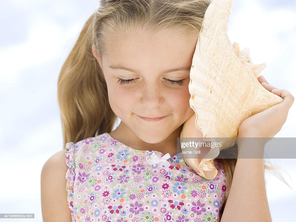 Girl (6-7) listening to seashell, close-up