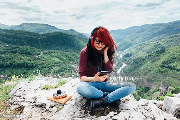 Fille écoutant de la musique au sommet de la montagne