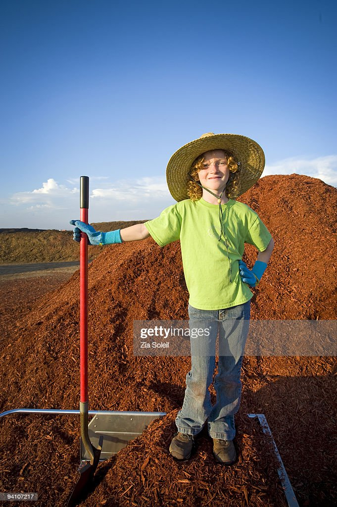 girl loading free mulch from municipal landfill : Stock Photo