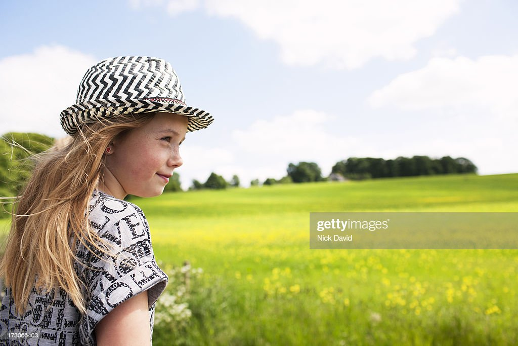 girl looking accross green field : Stock Photo