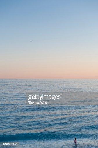 Girl looking across the water : Bildbanksbilder