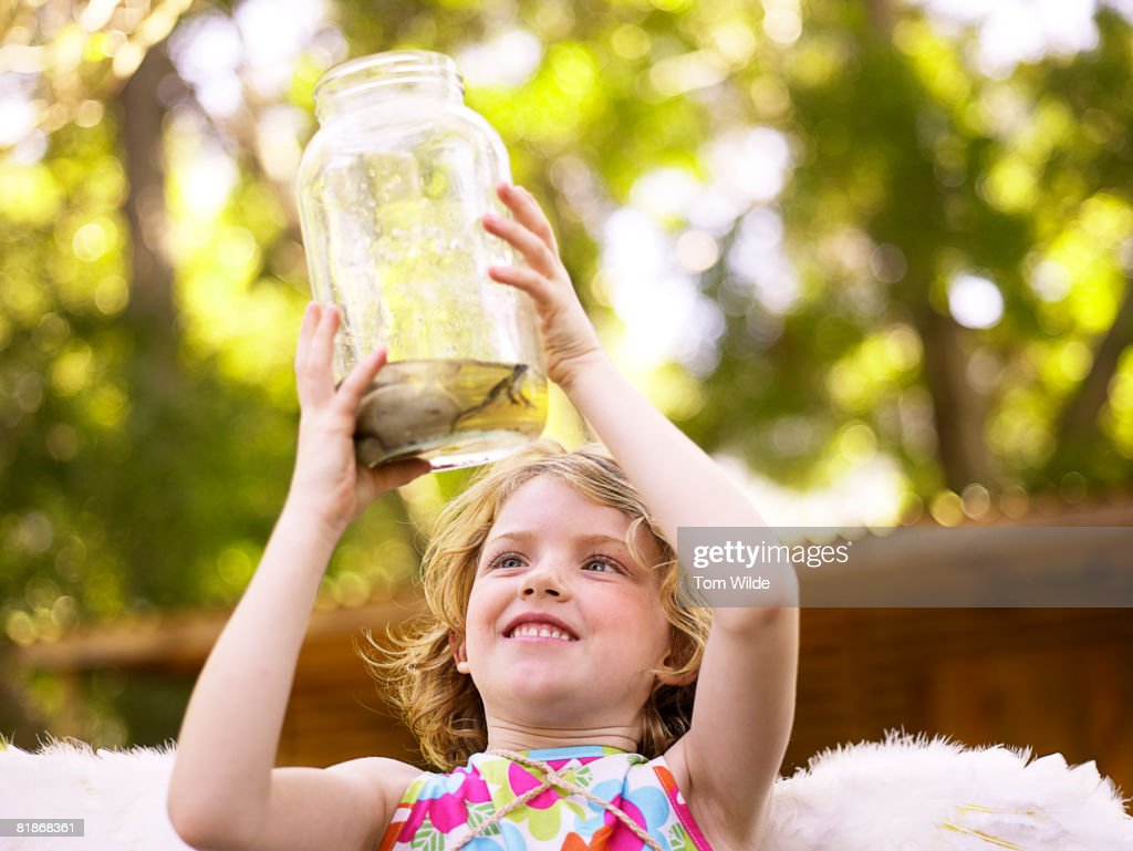 Girl looking at a frog in a jar : Stock Photo