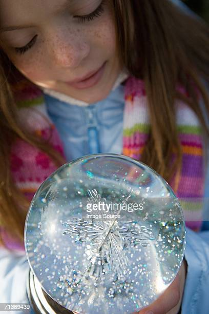 Girl looking at a snow dome