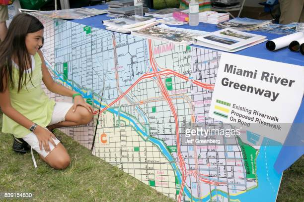 A girl looking at a street map at Miami River day