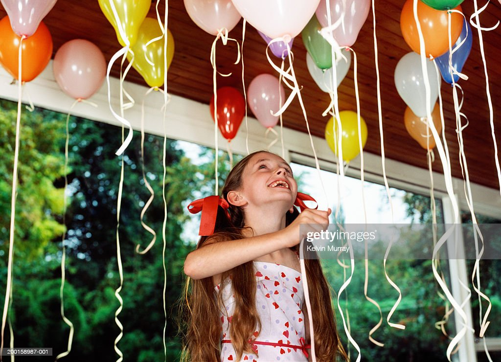Girl (10-12) looking at balloons on ceiling, holding balloon string : Stock Photo