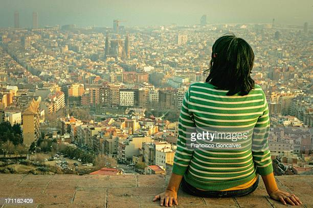 Girl looking at Barcelona skyline from above