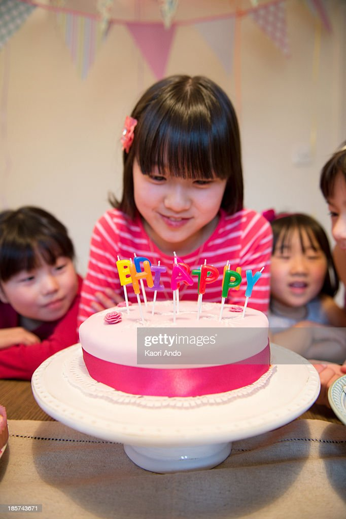Girl looking at birthday candles on cake : Stock Photo