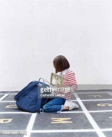 Girl (5-7) looking at book in playground : Stock Photo