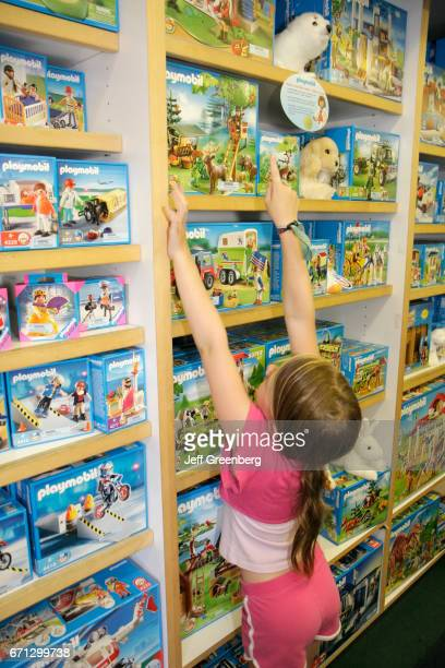 A girl looking at boxes of Playmobil in Toy Harbor