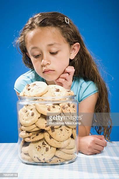 Girl looking at chocolate chip cookies in cookie jar