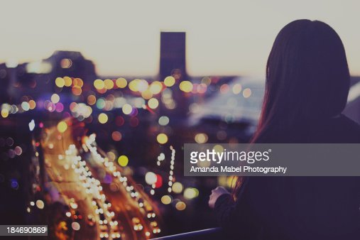 Girl looking at city night view of lights