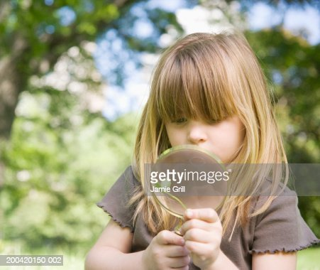 Girl (3-5) looking at clover through magnifying glass : Stock Photo