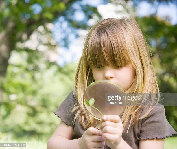 Girl (3-5) looking at clover through magnifying glass