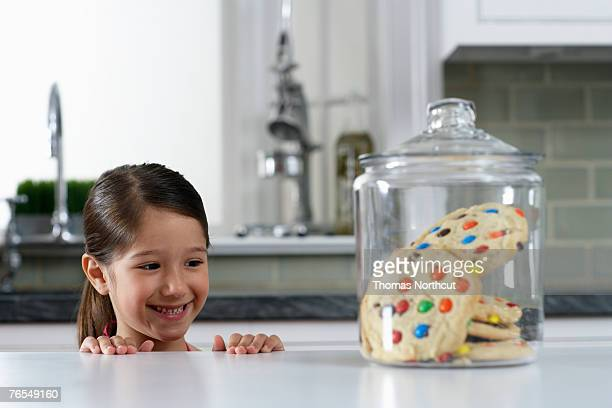 Girl (4-6) looking at cookie jar on kitchen counter