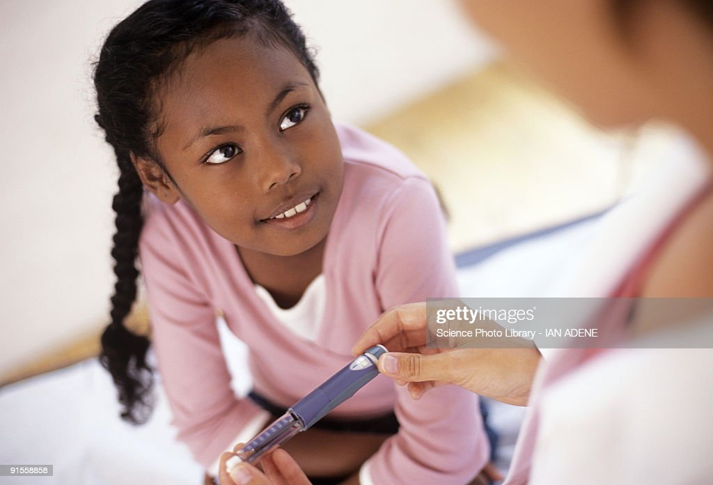 Girl (8-9) looking at doctor holding insulin syringe