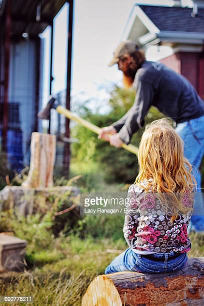 Girl Looking At Father Cutting Wood With Axe On Grassy Field
