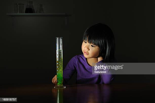 Girl Looking at Fizzing Green Chemical