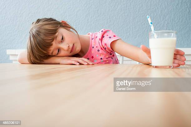 Girl looking at glass of milk
