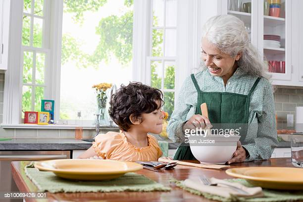 Girl (6-7 years) looking at grandmother preparing food in kitchen
