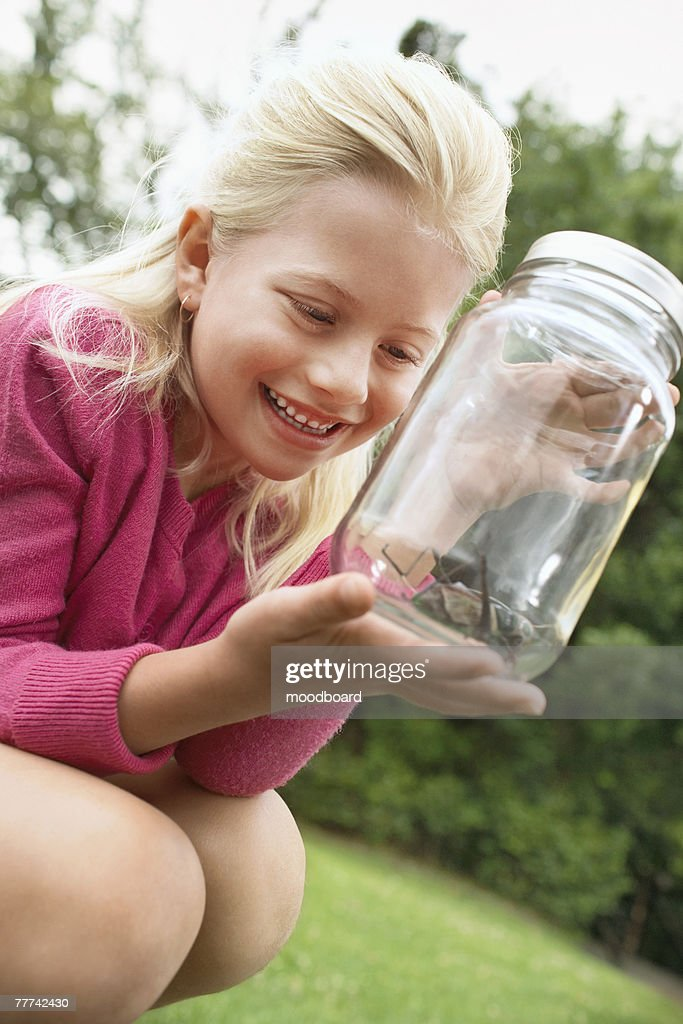 Girl Looking at Grasshopper in Jar : Stock Photo