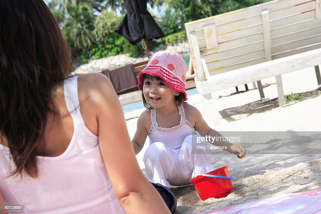 Girl looking at her mother and smiling on the beach : Stock Photo