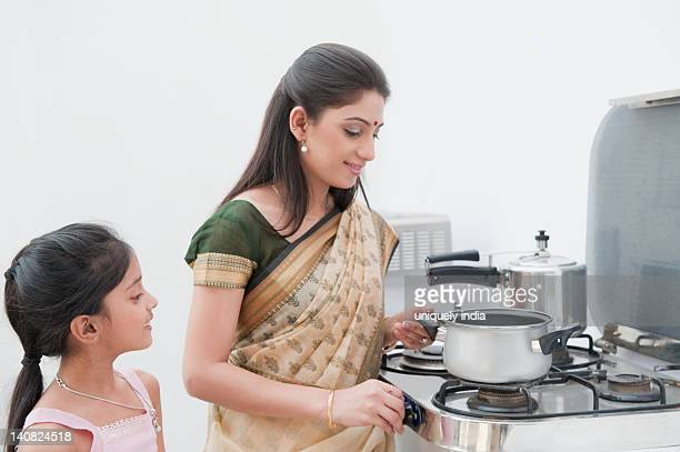 Girl looking at her mother cooking