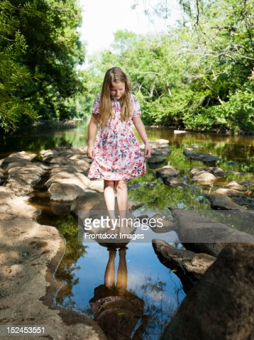 Girl looking at her reflection in the river : Foto de stock