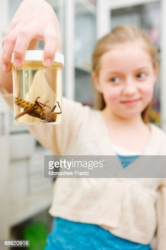 Girl looking at insect in jar in classroom : Stock Photo