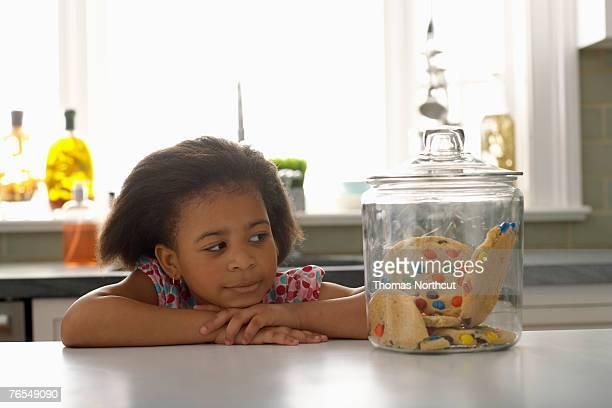 Girl (4-6) looking at jar of cookies